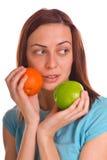 Holdingapfel und -orange der jungen Frau über Weiß lizenzfreies stockbild