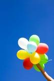 Holdingballone gegen blauen Himmel Stockfotografie