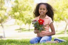 Holdingblumen des jungen Mädchens Lizenzfreies Stockfoto