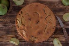 holdingen för closeupen för äpplebakgrund isolerade den stekheta piered som visar den vita kvinnan rund cake Pie med äpplen royaltyfria foton