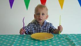 Holdinggabel und -messer des kleinen Jungen in der Hand und Tabelle schlagend Kardanringschu? stock video