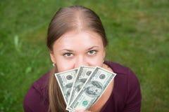Holdinggeld der jungen Frau lizenzfreie stockfotos