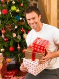 Holdinggeschenke des jungen Mannes vor Weihnachtsbaum Lizenzfreies Stockfoto