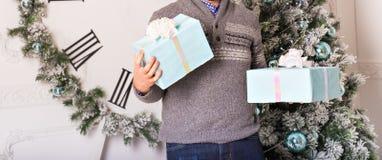Holdinggeschenke des jungen Mannes vor Weihnachtsbaum Stockbild