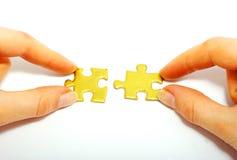 Holdinggoldpuzzlespiel stockfotos
