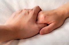 Holdinghände im Bett Lizenzfreie Stockfotos