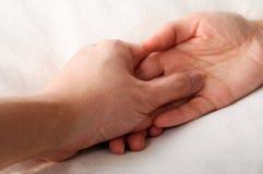 Holdinghände im Bett Stockfoto