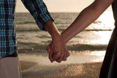 Holdinghände am Strand stockbild