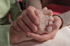 Holdinghand der jungen Frau der traurigen älteren Frau mit Rollstuhl lizenzfreie stockfotos
