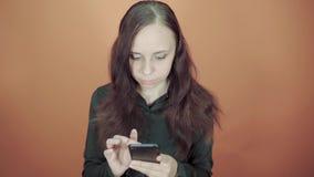 Holdinghandy der jungen Frau in der Hand auf orange Hintergrund Weiblich, eine Mitteilung auf einem Smartphone schreibend stock video