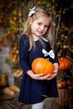 Holdingkürbis des kleinen Mädchens im Herbstinnenraum stockfoto