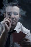 Holdingkarten und -zigarre des jungen Mannes im Rauche Lizenzfreies Stockfoto
