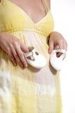 Holdingpaare der schwangeren Frau der weißen Schuhe Lizenzfreies Stockbild