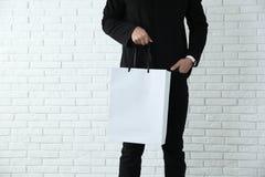 Holdingpapiertüte des jungen Mannes gegen Backsteinmauer Modell für Design lizenzfreie stockfotos