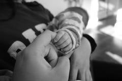Holdingshand met baby voor het eerst royalty-vrije stock afbeelding