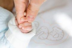 Holdingshanden van de baby en haar vader stock afbeeldingen