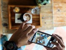 Holdingssmartphone neemt een foto van Latte-de kop van de kunstkoffie op het houten dienblad stock afbeeldingen