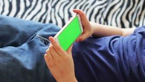 Holdingstouchscreen Apparaat, Close-up van jongenshanden die een slimme telefoon met behulp van chroma-sleutel, het groen-scherm stock footage