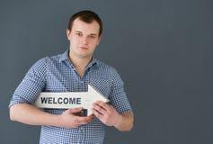 Holdingwillkommens-Brettfahne des jungen Mannes, stehend auf dunklem Hintergrund Lizenzfreie Stockfotos