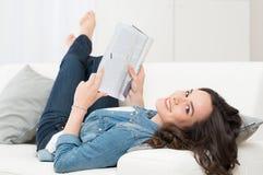Holdingzeitschrift der jungen Frau Lizenzfreie Stockfotos
