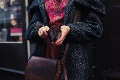 Holdiong de la mujer su cartera en la calle Imágenes de archivo libres de regalías