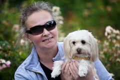 Holdiong maduro da mulher seu filhote de cachorro Foto de Stock Royalty Free