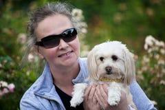 Holdiong maduro de la mujer su perrito Foto de archivo libre de regalías
