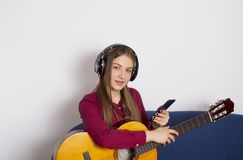 A girl in a red shirt -Holds an acoustic guitar and wants to play.. Holds an acoustic guitar and wants to play royalty free stock images