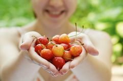 She holds a handful of cherries. Outside Royalty Free Stock Image