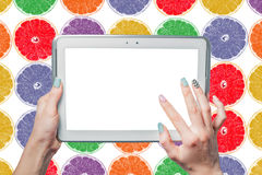 She holds a tablet on a background of citrus Stock Photography