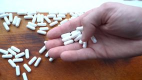 Holds white capsules, pills or vitamins scattered. On a wooden table royalty free stock image