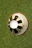 Into the hole. Golf ball in a hole Stock Photo