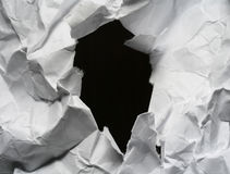 Hole. Large hole with black center in the high relief crushed white paper Stock Photo