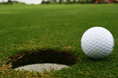 In the hole. Golf ball by the cup stock images