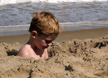 In The Hole Again!. A little boy sitting in a hole at the beach.. digging in the sand Stock Image