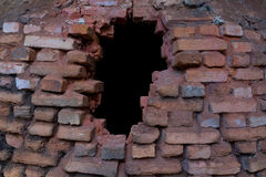 Hole in the ashes-covered brick stove. Black hole in the old red brick stove covered with dust and ashes Royalty Free Stock Images