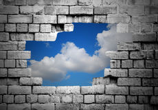 Hole in brick wall revealing clouds Royalty Free Stock Image