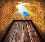 Hole in the brick wall of room with wooden floor Royalty Free Stock Photography