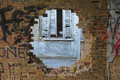 Hole in a brick wall. View of a hole in a damaged brick wall stock photo