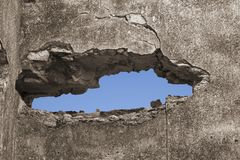 A hole in a broken wall with blue sky stock photo