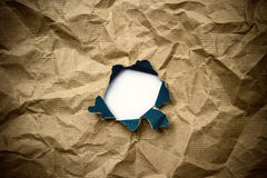 Hole in brown crumpled wrapping paper Stock Photos