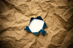 Hole in brown crumpled wrapping paper Royalty Free Stock Photos