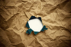 Hole in brown crumpled wrapping paper Royalty Free Stock Photo