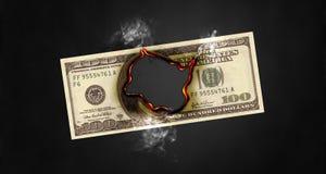 Hole Burning Through Hundred Dollar Bill. Flaming and smoking hole burning through a one hundred dollar bill Royalty Free Stock Photo