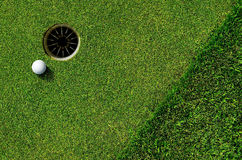 In the hole. Close up of a golf ball and the hole Royalty Free Stock Images