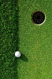 In the hole. Close up of a golf ball and the hole Stock Photo