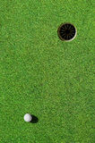 In the hole. Close up of a golf ball and the hole Stock Photos