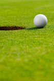 In the hole. Close up of a golf ball close to the hole Royalty Free Stock Images