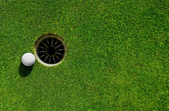 In the hole. Close up of a golf ball close to the hole Royalty Free Stock Photography