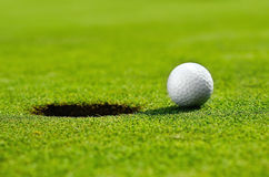 In the hole. Close up of a golf ball close to the hole Royalty Free Stock Photos
